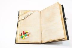 Tabletten op het boek Stock Afbeeldingen