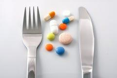Tabletten op plaat met vork en mes Stock Afbeelding