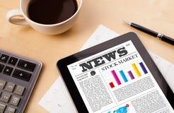 Tabletten-PC zeigt Nachrichten auf Schirm mit einem Tasse Kaffee auf einem Schreibtisch Stockfotos