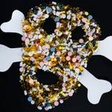 Tabletten, Pillen und Kapseln, die einen gruseligen Schädel formen , lokalisiert auf schwarzem Hintergrund Lizenzfreies Stockfoto