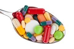 Tabletten und Medizin auf Löffel Stockfotografie