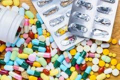Tablettenfläschchen, das an Pillen und leere Blisterpackung zur Oberfläche verschüttet Stockfotografie