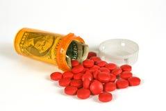 Tablettenfläschchen mit Bargeld-Krankheitskosten-Konzept Lizenzfreie Stockfotografie