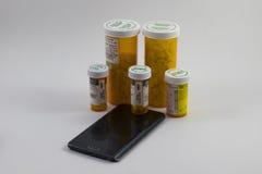 Tablettenfläschchen und ein Handy Lizenzfreies Stockbild