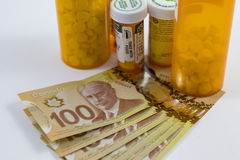 Tablettenfläschchen und kanadische Geld-Hunderte Lizenzfreie Stockbilder