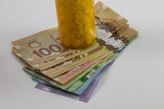 Tablettenfläschchen und kanadische Geld-Hunderte Stockbild
