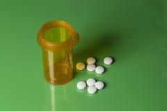 Tablettenfläschchen und Pillen auf einer Grün eingestuften Platte Stockbild