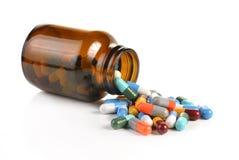 Tablettenfläschchen, das an Pillen zur Oberfläche lokalisiert auf einem weißen BAC verschüttet Lizenzfreie Stockfotografie