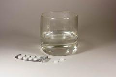 Tablettes avec un verre de l'eau Photos libres de droits