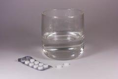 Tablettes avec un verre de l'eau Photo libre de droits