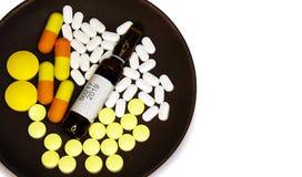 Tablettes, capsules et ampoules avec la médecine d'un plat Photos stock