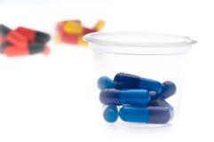 Tablettes colorées, capsules dans une cuvette Photographie stock