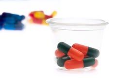 Tablettes colorées, capsules dans une cuvette Photo libre de droits
