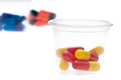 Tablettes colorées, capsules dans une cuvette Photos libres de droits