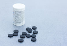 Tablettes de charbon actif pour nettoyer le corps sur Gray Background Closeup Photographie stock