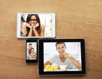 Tablettes de Digitals et téléphone intelligent avec des images sur un bureau Image libre de droits