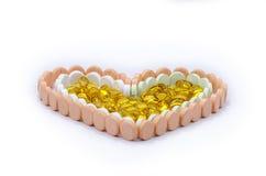 Tablettes et capsules dans la forme de coeur. photos stock