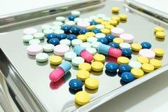 Tablettes et capsules de drogue sur le plateau de médicament Photos libres de droits
