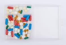 Tablettes et capsules pour la boîte en verre de médecines Photos libres de droits