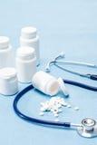 Tablettes et stéthoscope renversés par fournitures médicales Images stock