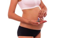 Tablettes pendant la grossesse Dans les mains femelles dans la perspective de l'abdomen image stock