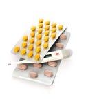 Tablettes pour le traitement de la maladie et du thermomètre sur le blanc Photographie stock libre de droits