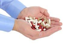 Tablettes rouges et blanches dans des mains mâles Images stock