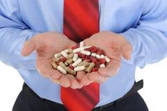 Tablettes rouges et blanches dans des mains mâles Images libres de droits