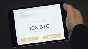 Tablettoepassing die het saldo van een Bitcoin-portefeuille tonen voorraad Digitaal muntconcept Saldo van bitcoins op stock video