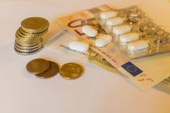 Tabletts blanco con los billetes de banco y las monedas de los euros Concepto Pharmaceu Imagen de archivo