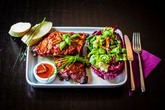 Tableview of spareribs with salad, chili sauce and baguette on w Royalty Free Stock Photo
