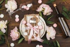 Tableware и silverware с тучным светом - розовыми пионами на деревянной предпосылке Стоковые Фото