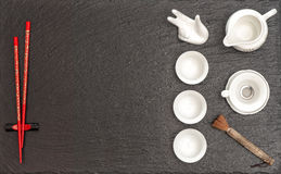 Tableware for asian tea ceremony. Teapot, cups and red chopstick Royalty Free Stock Photos