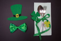 Tableware on blackboard in St. Patricks Day. Cutlery with green ribbon Royalty Free Stock Images