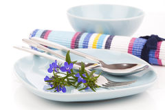 Tableware with blue lobelia flowers and cutlery Stock Photography