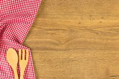 Tableware and checkered red cloth napkin on wooden background. Top view with space for your text Royalty Free Stock Image
