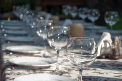 Tableware. Empty footed tumblers,glasses and party plates on festive served table Royalty Free Stock Image