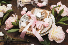 Tableware with light pink peonies and meringues. Table serving: tableware and silverware with decorations. Light pink peonies and meringues on the wooden Stock Photography