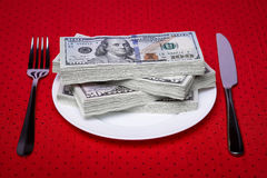 Tableware paper money. Bundle of dollars on a plate, paper money, an economic concept, serving business lunch, a red tablecloth in a black polka dots Stock Photos