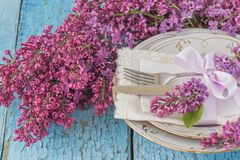 Tableware and silverware with bouquet of light violet lilac Royalty Free Stock Images