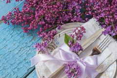 Tableware and silverware with bouquet of light violet lilac Royalty Free Stock Photos