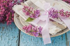Tableware and silverware with bouquet of light violet lilac Stock Image
