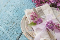 Tableware and silverware with bouquet of light violet lilac Royalty Free Stock Image