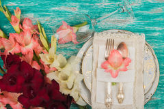 Tableware and silverware with light pink gladiolus on the azure background Royalty Free Stock Image