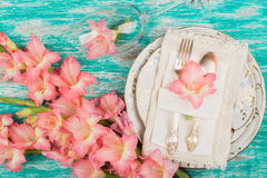 Tableware and silverware with light pink gladiolus on the azure background Stock Photos