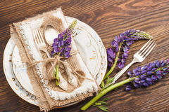 Tableware and silverware with puffy violet lupins Stock Photos