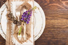 Tableware with violet lupines and silverware. On the wooden background Royalty Free Stock Photo
