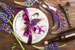 Tableware with violet lupinus and silverware. With different decorations on the wooden background stock photography