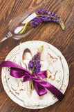 Tableware with violet lupinus and silverware. On the wooden background royalty free stock image