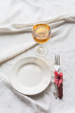 Tableware, white plate, fork, knife, juice on a white tablecloth Stock Photos